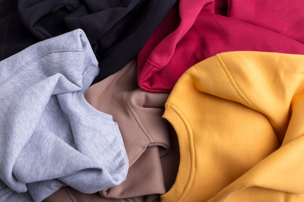 A pile of solid color sweatshirts.